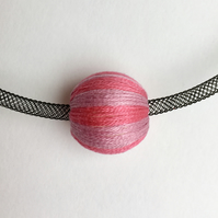 Contemporary black mesh tube necklace with pink thread wrapped bead.