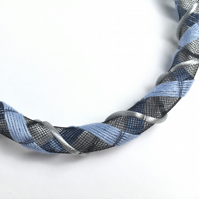 Contemporary black and pale blue embroidered mesh necklace.