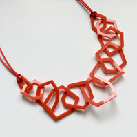 Statement red acrylic geometric necklace.