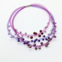 Pink and lilac and purple beaded three strand necklace.