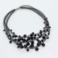 Black three strand faceted bead necklace.