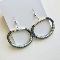 Modern pale grey and black mesh and cord pendant earrings.