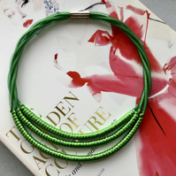 Contemporary emerald green cord three strand necklace.