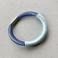 Pale blue cord and navy tube bracelet.