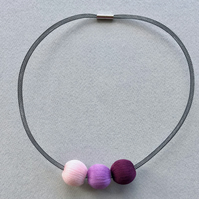 Contemporary pink, purple and lilac bead necklace.