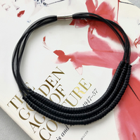 Black cord contemporary necklace.