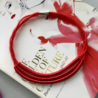 Contemporary red three strand cord necklace.