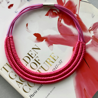 Pink cord three strand contemporary necklace.