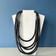 Contemporary black multi strand cord and mesh tube necklace.