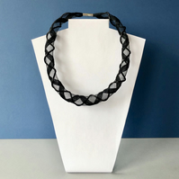 Black embroidered tubular collar necklace.