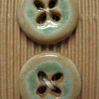 2 ceramic circular blue and brown buttons with four-leaf clover shaped holes