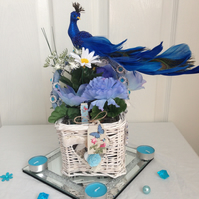 Blue cream wicker basket design with silk peacock placed on top.