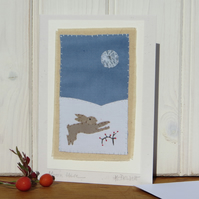 Miniature hand-stitched scene of a leaping hare and moon with berries