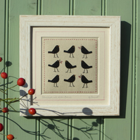 Small framed hand-stitched textile of blackbirds with bright red berries
