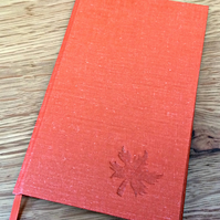 Slim orange hardback notebook with debossed leaf motif on cover
