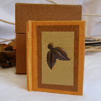Miniature hardback blank book and case in orange, brown and gold with metal leaf