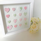 White box frame encasing small embossed handmade clay hearts.
