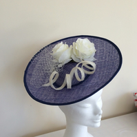 Blue saucer hat trimmed with light cream roses and a sinamay twist