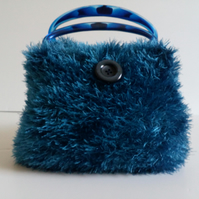Blue knitted handbag, lined and with blue plastic handles, eyelash yarn