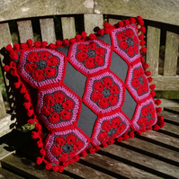 A stunning crocheted and sewn cushion in grey, pink and red. In soft merino wool