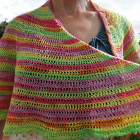 A lightweight cotton crocheted shawl wrap in vibrant multi colours