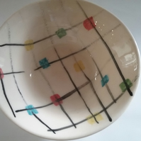 Ceramic pottery bowl hand-thrown and hand-painted with cheerful check pattern.
