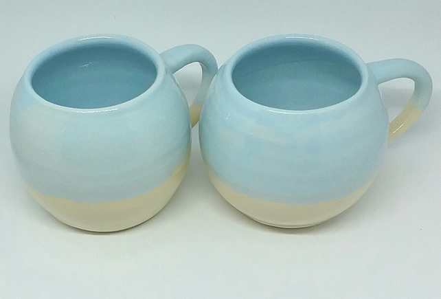 Handmade ceramic mug with pale blue and clear glaze on handthrown white clay