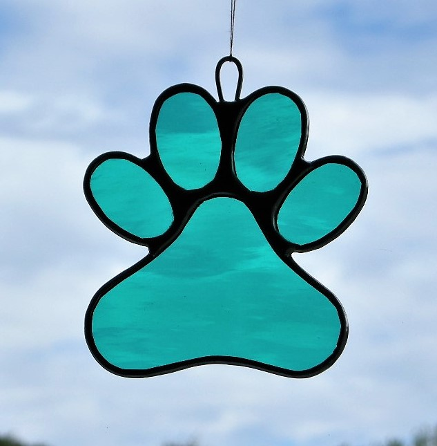 Paw Print in teal green rippling water glass