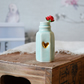 Small Glazed Flat Sided Bottle with a Gold Embossed Heart and A Red Paper Rose