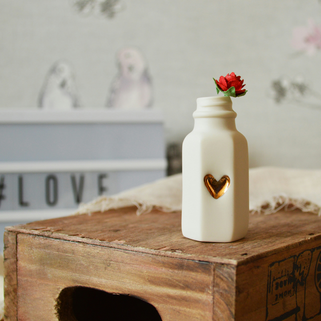Small Flat Sided White Bottle With A Gold Embossed Heart And A Red Paper Rose