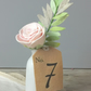 pale pink handdyed roes in ceramic mini milk bottle with table number tag