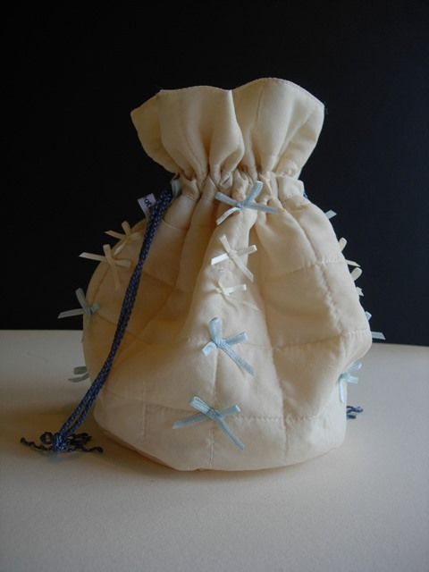 Vintage ivory silk quilted dolly bag blue bows and cords.