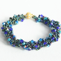 Spiral rope bracelet with blue, green and turquoise crystals; gold plated clasp