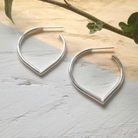 Small lotus petal hoops in recycled sterling silver.