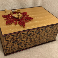 Gold and burgundy box filled with tealights