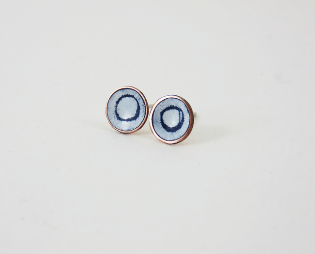Round copper stud earrings with blue and white enamel and drawn detail.