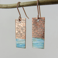 Textured copper dangle earrings with blue and white enamel
