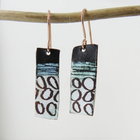 Dangle enamel on copper earrings with hand drawn pattern detail.