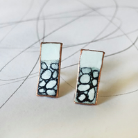 Rectangle white and black enamel and copper studs with hand drawn detail.