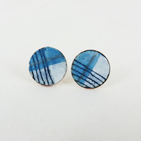 Round copper stud earrings with blue, white and silver enamel and drawn detail.