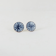 Round copper stud earrings in blue and white enamel with hand drawn detail.