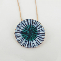 Round enamel and copper pendant with a green pool.