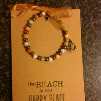 Stretch bracelet, hand strung, with charm attached, on an A6 card.