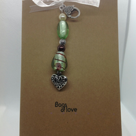 Hand made bag charm attached to a hand stamped greetings card