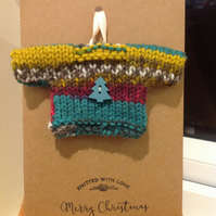Handmade mini sweater attached to card with envelope.