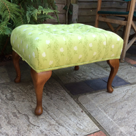 Footstool in a pale green floral fabric