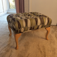 Buttoned footstool covered in a retro fabric