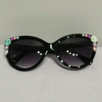 Black Up-cycled sunglasses with pink bows, flowers and pearls.