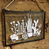 Cactus paper cut design in glass hanging frame.