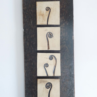 Unfolding fern tiles mounted onto rustic recycled vintage wood.